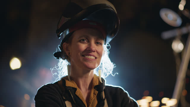 slo mo cu portrait of an experienced female welder smiles at the camera - entrepreneur stock videos & royalty-free footage
