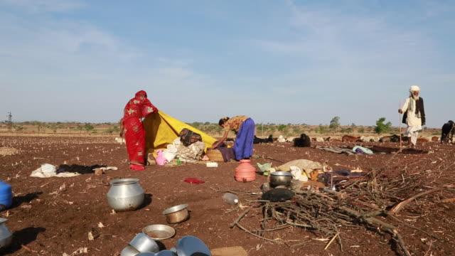 portrait of an indian woman with a traditional red scarf she is sitting outside at a campfire site of an dry field and is cooking as hindu woman she... - bindi stock videos and b-roll footage