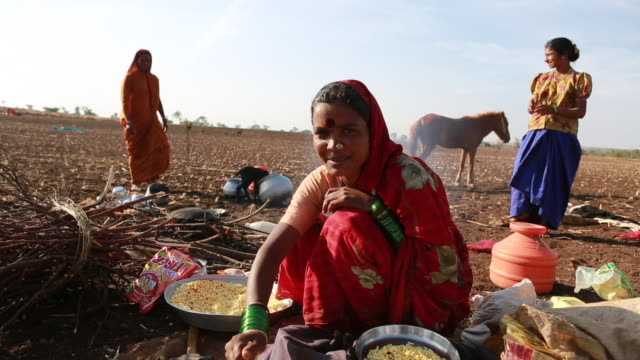 Portrait of an indian woman with a traditional red scarf She is sitting outside at a campfire site of an dry field and is cooking The food can be...