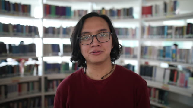 vídeos de stock e filmes b-roll de portrait of an malay man smiling in the school library - east asian ethnicity