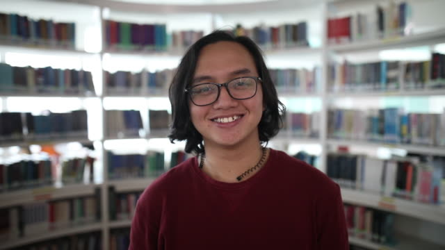 portrait of an malay man smiling in the school library - malaysian ethnicity stock videos & royalty-free footage