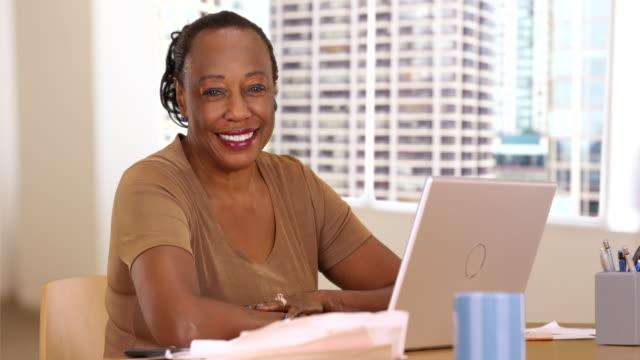 a portrait of an older black woman at work using her laptop - weibliche angestellte stock-videos und b-roll-filmmaterial