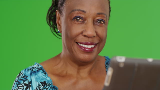 a portrait of an older black woman using her tablet on green screen - maestra video stock e b–roll
