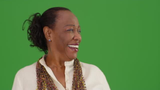 a portrait of an older woman standing on green screen - hüfte stock-videos und b-roll-filmmaterial