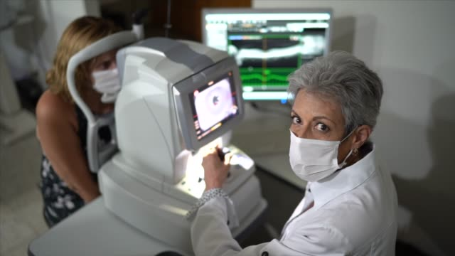 portrait of an ophthalmologist doing an eye exam - optical equipment stock videos & royalty-free footage