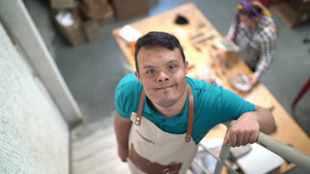 portrait of an special needs employee in a wooden toys' factory - persons with disabilities stock videos & royalty-free footage