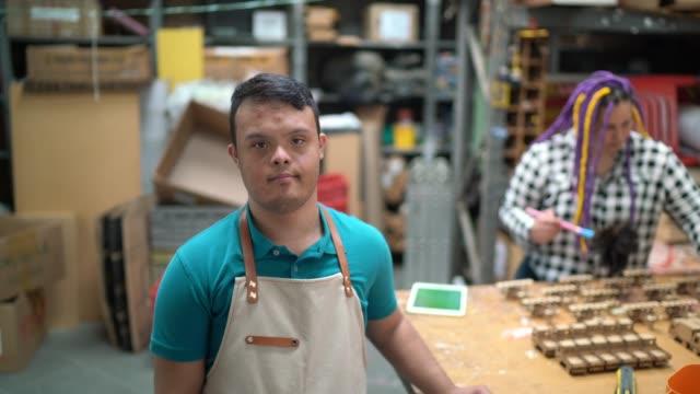 vidéos et rushes de verticale d'un employé de besoins spéciaux dans une usine de jouets en bois - personnes avec déficiences