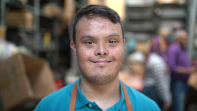 portrait of an special needs employee in a wooden toys' factory - down's syndrome stock videos & royalty-free footage