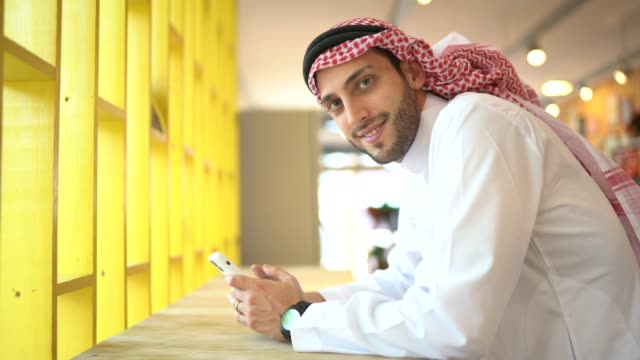 portrait of arab middle east man using mobile phone at convenience store - middle eastern culture stock videos & royalty-free footage