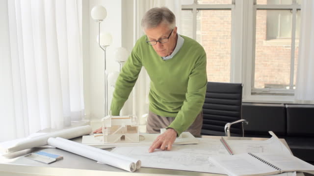 MS Portrait of architect standing behind his desk with blueprints / New York City, New York, USA