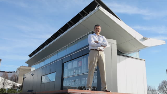 WS Portrait of Architect with Blueprints Standing in Front of Solar Building / Richmond, Virginia, USA