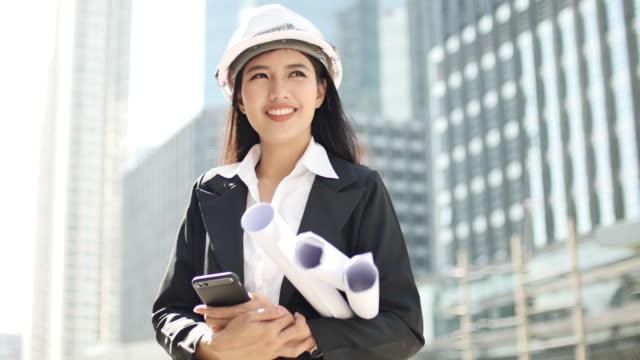 vídeos y material grabado en eventos de stock de retrato de arquitecto asiático con casco sonriendo a la cámara en el sitio de construcción - arquitecta