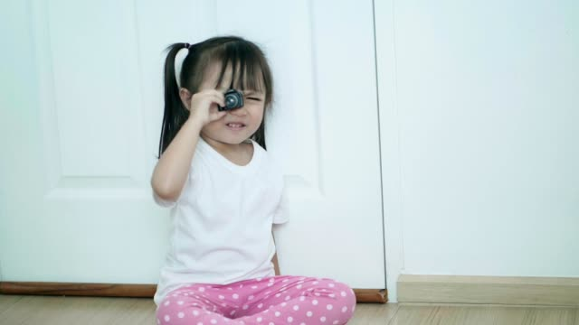 Portrait of Asian baby girls playing camera while sitting on the floor with positive emotion