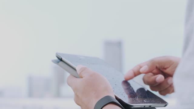 porträt von asiatischen geschäftsmann lesen nachricht mit smartphone im freien. konzept von jungen menschen, die mobile geräte arbeiten. - flugpassagier stock-videos und b-roll-filmmaterial