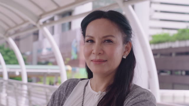 vidéos et rushes de portrait de femme d'affaires asiatique a infecté des hommes âgés 30-40 ans sur la ville sur le fond, emprunté et tourné pour sourire à la caméra. - adulte d'âge mûr