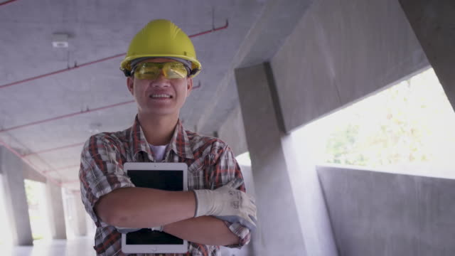 portrait of asian construction engineer in hardhat holding digital tablet computer at construction site, engineers at work checking construction building project on site, looking at camera - thai ethnicity stock videos & royalty-free footage