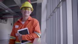Portrait of Asian Construction or Electronics engineer in hardhat wearing safety jacket holding digital tablet computer next to window at construction site, Engineers at work checking construction building project on site, Looking at camera