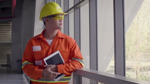portrait of asian construction or electronics engineer in hardhat wearing safety jacket holding digital tablet computer next to window at construction site, engineers at work checking construction building project on site, looking at camera - thai ethnicity stock videos & royalty-free footage