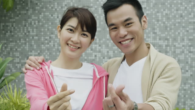 portrait of asian couple doing the love sign - taipei stock videos & royalty-free footage
