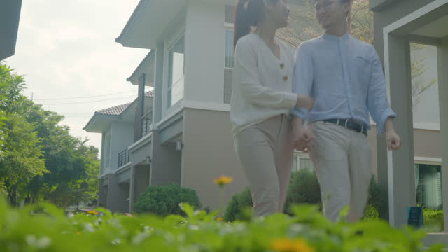 portrait of asian couple walking and hugging together looking happy in front of their new house to start new life. family, age, home, real estate and people concept. - new age stock videos & royalty-free footage