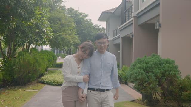 vidéos et rushes de verticale de couples asiatiques marchant et étreignant ensemble regardant heureux devant leur nouvelle maison pour commencer une nouvelle vie. la famille, l'âge, la maison, l'immobilier et le concept de personnes. - new age concept