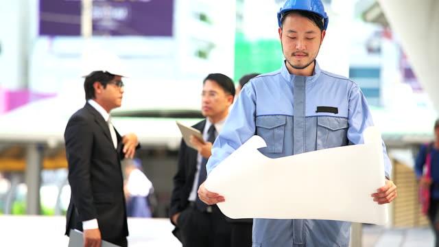 バック グラウンドで会議ビジネス人々 のグループで青写真を持ってアジアのエンジニアの肖像画。 - ホワイトカラー点の映像素材/bロール