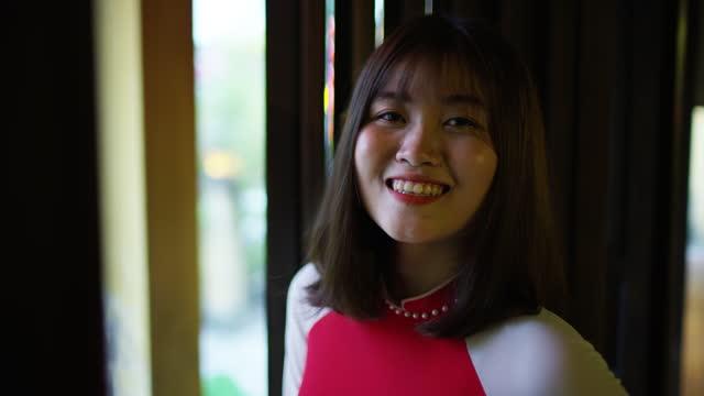 portrait of asian female with friendly smile vietnam - 赤のドレス点の映像素材/bロール