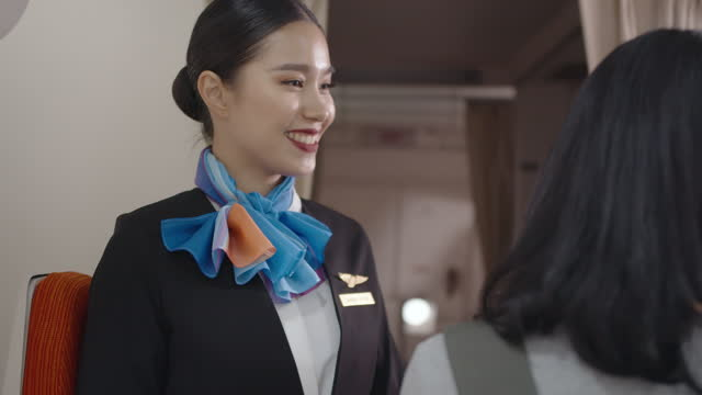 portrait of asian flight attendant greeting welcome to passenger, smiling and looking at camera - crew stock videos & royalty-free footage