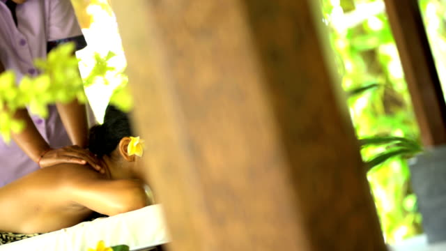 portrait of asian girl relaxing at balinese spa - spa treatment点の映像素材/bロール