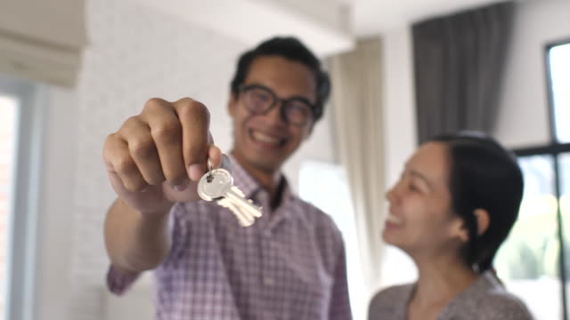 portrait of asian happy couple standing in new home with keys - key stock videos & royalty-free footage
