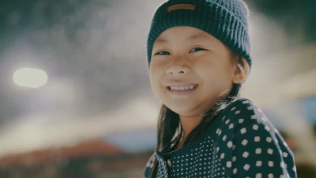 vidéos et rushes de portrait d'asiatique petite fille regardant l'appareil photo dans la neige - joie