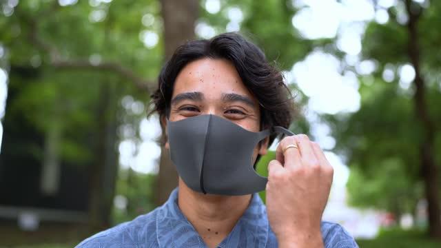 顔からマスクを外すアジア人男性の肖像。コロナウイルスの概念の終わりのためのビデオ。 - absence点の映像素材/bロール