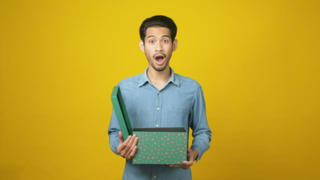 portrait of asian man unbox and surprise for the present while standing over isolated yellow background at studio, happy asia male opening the gift box - unwrapping stock videos & royalty-free footage