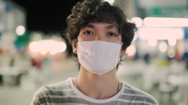 亞洲男子與面具的肖像 - 行人路 個影片檔及 b 捲影像