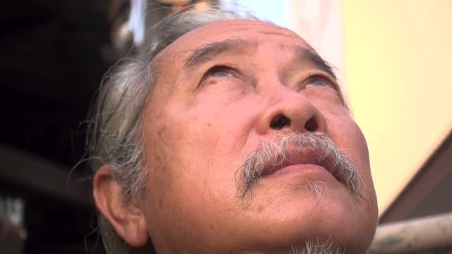portrait of asian senior guy thinking. - sad old asian man stock videos & royalty-free footage