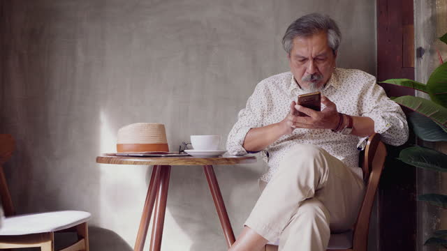 portrait of asian senior man using smart phone while sitting at coffee shop cafe, senior man typing an sms message and working mobile devices, people lifestyle technology concept - hipster culture stock videos & royalty-free footage
