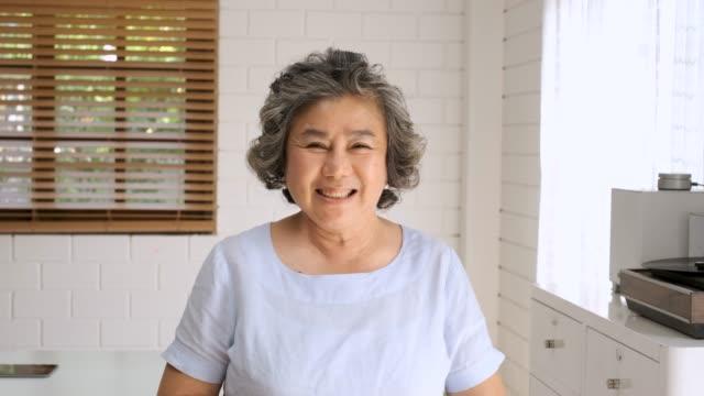 カメラを見て、自宅でリビングルームで笑顔アジアシニア女性の肖像画.ホームコンセプトで幸せな老化 - 中国人点の映像素材/bロール