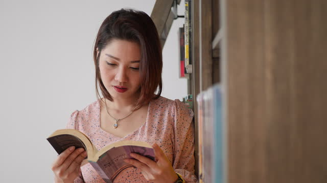portrait of asian woman reading analog books at home - book cover stock videos & royalty-free footage