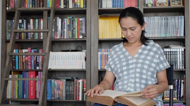 vidéos et rushes de verticale de femme asiatique affichant des livres analogiques à la maison - littérature