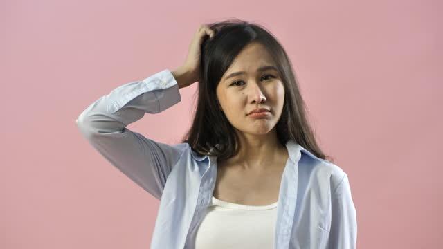 ピンクの背景の上に孤立した彼女の頭の否定的な思考を掻くアジアの女性の肖像画 - 問う点の映像素材/bロール