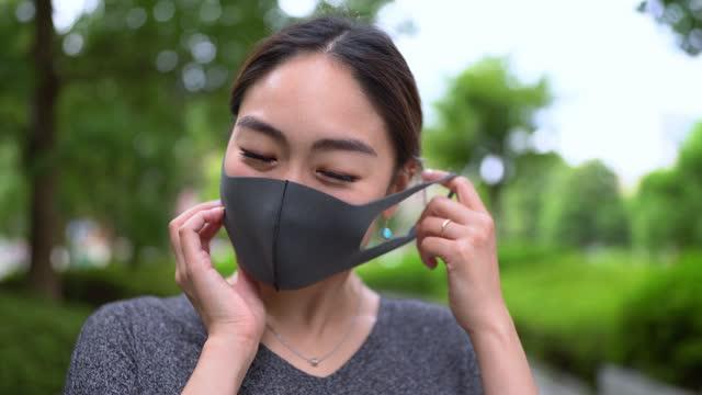 顔からマスクを外すアジア女性の肖像。コロナウイルスの概念の終わりのためのビデオ。 - absence点の映像素材/bロール