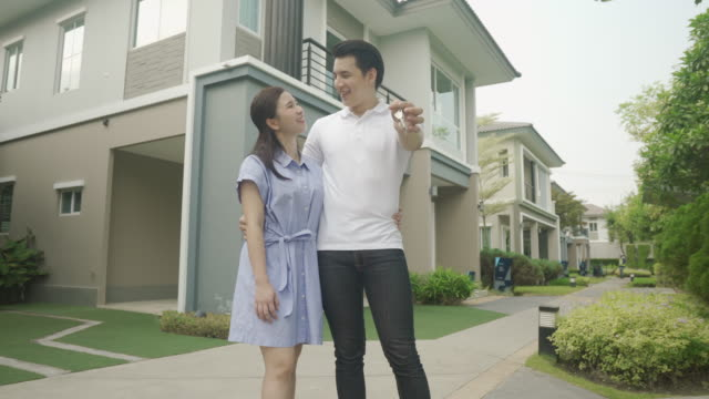 portrait of asian young couple standing and hugging together and holding house key looking happy in front of their new house to start new life. family, age, home, real estate and people concept. - house key stock videos & royalty-free footage
