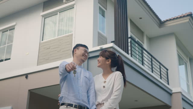 portrait of asian young couple standing and hugging together and holding house key looking happy in front of their new house to start new life. family, age, home, real estate and people concept. - standing stock videos & royalty-free footage