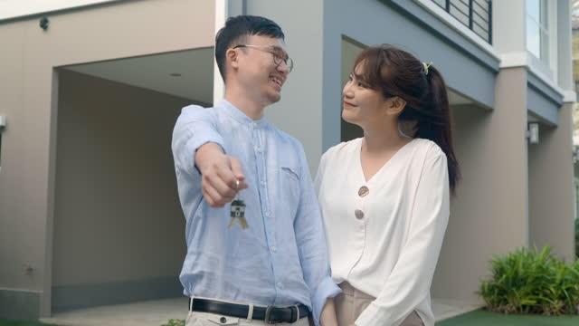 vidéos et rushes de verticale des jeunes couples asiatiques restant et étreignant ensemble et tenant la clé de maison regardant heureux devant leur nouvelle maison pour commencer la nouvelle vie. la famille, l'âge, la maison, l'immobilier et le concept de personnes. - new age concept