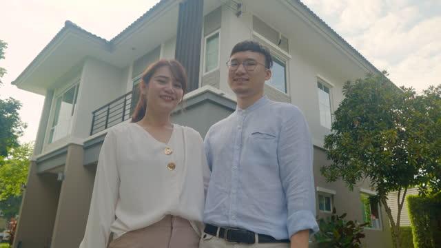 vídeos y material grabado en eventos de stock de retrato de la joven pareja asiática de pie y abrazándose juntos luciendo felices frente a su nueva casa para comenzar una nueva vida. concepto de familia, edad, hogar, bienes raíces y personas. - new age
