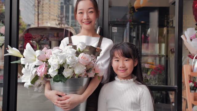 vidéos et rushes de portrait de la jeune mère asiatique avec la fille de 10 ans sont propriétaire boutique de fleurs debout tout en regardant la caméra à la boutique ouverte après le verrouillage et l'épidémie de coronavirus covid-19. petite entreprise - new age concept