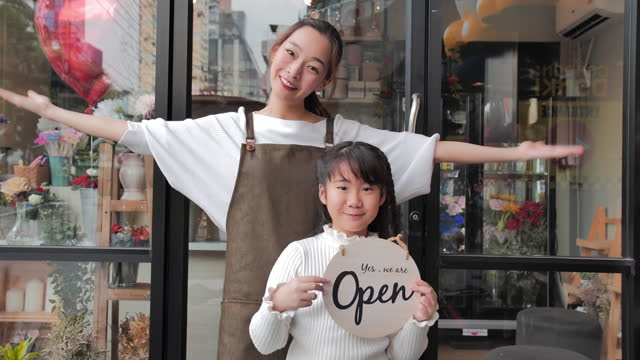 portrait of asian young mother with daughter age 10 yearold are owner flower shop standing while looking at camera at shop open after lockdown and epidemic of coronavirus covid-19.small business - new age stock videos & royalty-free footage