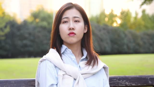 4K: Porträt der jungen Asiatin, die lächelnde Sonne Streulicht im Park, Shanghai, China