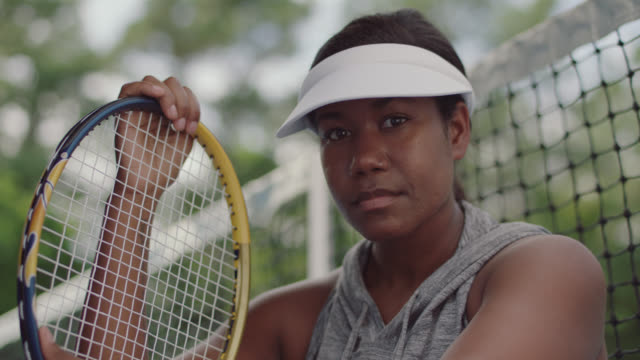 slow mo. cu. portrait of athletic female tennis player sitting on a tennis court looking down at the court and looks up at the camera - sun visor stock videos and b-roll footage