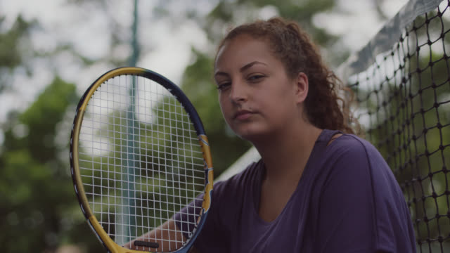 slow mo. cu. portrait of athletic female tennis player sitting on a tennis court glaring into the camera - tennis racket stock videos & royalty-free footage
